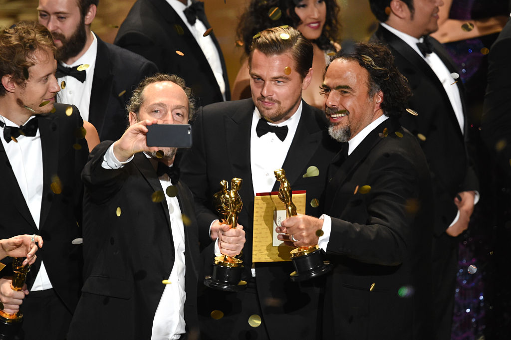 HOLLYWOOD, CA - FEBRUARY 28:  (L-R) Cinematographer Emmanuel Lubezki, actor Leonardo DiCaprio and director Alejandro Gonzalez Inarritu, all winners for 'The Revenant,' take a selfie onstage during the 88th Annual Academy Awards at the Dolby Theatre on February 28, 2016 in Hollywood, California.  (Photo by Kevin Winter/Getty Images)