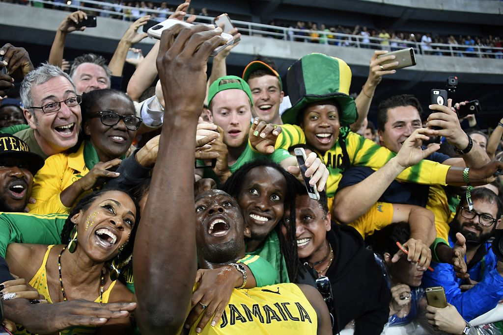 TOPSHOT - Jamaica's Usain Bolt takes selfie photos as he celebrates with fans after winning the Men's 200m Final during the athletics event at the Rio 2016 Olympic Games at the Olympic Stadium in Rio de Janeiro on August 18, 2016.   / AFP / Damien MEYER        (Photo credit should read DAMIEN MEYER/AFP/Getty Images)