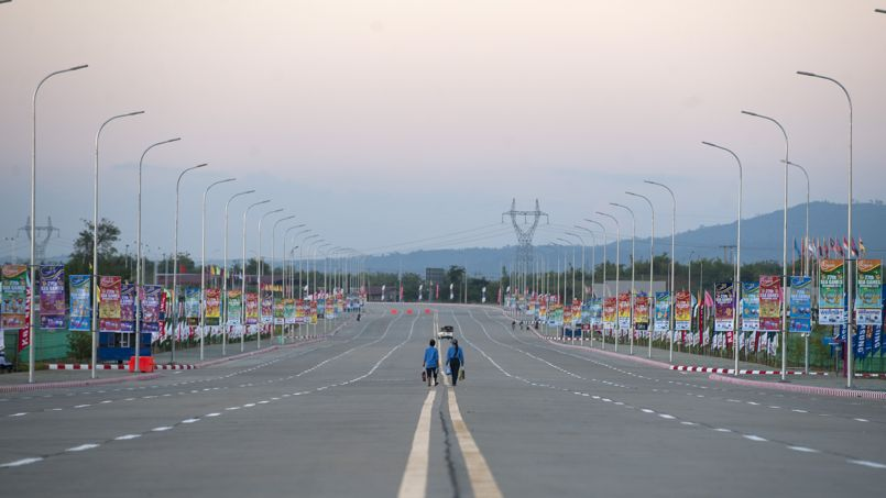 """In this picture taken on November 30, 2013, people walk past the sport centers ahead of the Southeast Asian Games (SEA Games) in Naypyidaw. Myanmar is """"100 percent"""" ready for the Southeast Asian Games, a senior official said on November 28, as the clock ticked down to the biggest sports event in the nation's troubled history. AFP PHOTO / YE AUNG THU"""